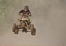 Quad bike race. Man on Quad bike racing trough dust Stock Image