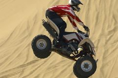 Quad bike rider in mid-air over sand Stock Photography