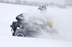 The quad bike's driver rides over snow track Stock Photo