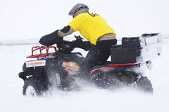 The quad bike's driver rides over snow track Stock Images