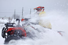 The quad bike's driver rides over snow track Stock Photography