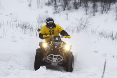 The quad bike's driver rides over snow track Royalty Free Stock Photo