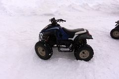 Quad bike in the snow ATV is a yellow color. ATV rentals royalty free stock photography