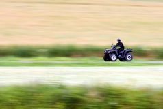 Quad bike and speed. Panning shot of a fast moving black ATV - quad bike Royalty Free Stock Image