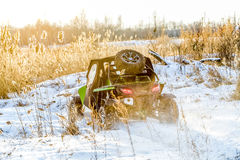 Quad bike on a winter in field off road. Green flashy quad bike on a winter in field off road in sunlight back view Stock Photo