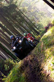 Quad bikes racing in forest. Angled view of men racing quad bikes in sunlit forest Royalty Free Stock Photo