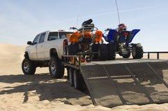 Quad Bikes On Trailer. Behind pickup truck in desert Stock Image
