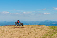 Quad biking in the mountains. Equipped ATV driver Stock Photography