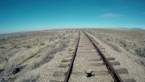 Quad copter shadow in old rustic railroad. Steel train tracks and wood ties in gravel and drone shadow stock footage
