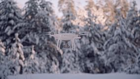 Quad copter unmanned camera hovers in frozen sky above forest on back. Ground. Carbon Drone with GPS. White quadrupter floats in the air, quadrocopter flies stock video