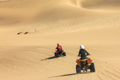 Quad driving people - two happy bikers in sand desert. royalty free stock photos