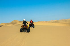 Quad driving people - two happy bikers in sand desert. Stock Photos