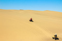 Quad driving people - two happy bikers in sand desert. Royalty Free Stock Photography