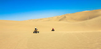Quad driving people - two happy bikers in sand desert. Royalty Free Stock Image
