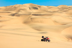 Quad driving in sand desert. ATV in middle of nowhere. Stock Images