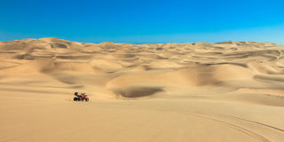 Quad driving in sand desert. ATV in middle of nowhere. Royalty Free Stock Images