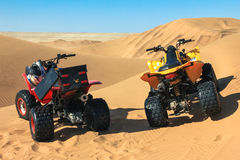 Quad driving in sand desert. Two ATV in middle of nowhere. Royalty Free Stock Photography