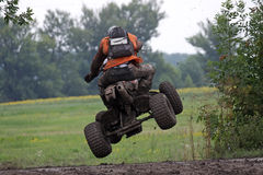 Prepare for landing. Quad racer jumping on a muddy offroad race - rear view Royalty Free Stock Images