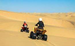 Quad l'azionamento della gente - due motociclisti felici nel deserto della sabbia Fotografia Stock