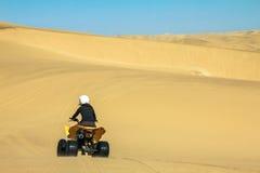 Quad l'azionamento della gente - motociclista felice nel deserto della sabbia Fotografia Stock