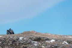Quad la bici ATV nell'inverno su una roccia Fotografia Stock