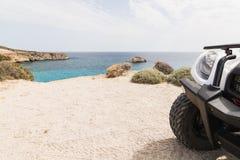 Quad la bici che sta sulla strada della spiaggia sull'isola di Milo, Grecia fotografie stock