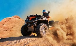 Quad la bici in nuvola di polvere, cava della sabbia su fondo fotografia stock