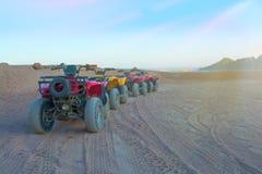 Quad le bici nel deserto davanti ed alle montagne fotografia stock