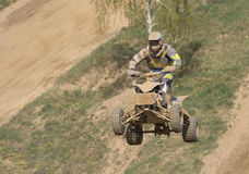 Quad racer is high jumping. Horizontally. Stock Photography