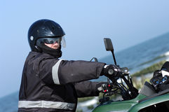 Quad rider (ATV). A man wearing black protective outfitm sitting on a large quad vehicle. (ATV Stock Image