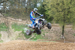 Quad rider is high jumping in the difficult terrain Stock Images