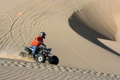 Quad rider in sand dunes bowl. Quad rider making his way around bowl at the sand dunes stock image
