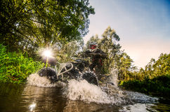 Quad rider through water stream royalty free stock images