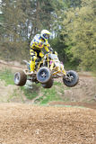 Quad rider in yellow is high jumping. Vertically. Stock Photography
