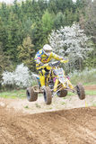 Quad rider in yellow is jumping. Vertically. Royalty Free Stock Photography