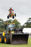 Quad stunt jump. WEEDON, UK - AUGUST 28: One of the riders of the stunt duo, Kangaroo Kid, team jumps his ATV over a line of parked cars and an earth mover at Stock Photography