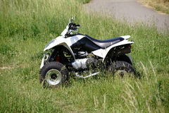 Quad in the terrain. A quad terrain vehicle standing on a meadow in the field Stock Images