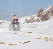 Quad throwing snow all over Royalty Free Stock Images