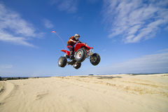 Quadbike jumping dunes stock photos