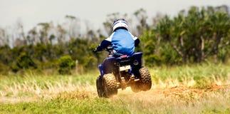 Quadbike racing. Boy on quadbike racing down dirt road Stock Image