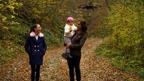 Quadcopter射击一幸福家庭 有她的他们走的两儿童步行的一个年轻母亲通过秋天森林 影视素材