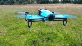 Quadcopter azul no fundo da grama verde imagem de stock