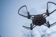 Quadcopter-Brummen, das in einem blauen Himmel schwebt lizenzfreie stockbilder