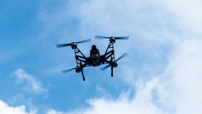 Quadcopter with camera flying on a clear sunny sky sunset backgr Stock Photos