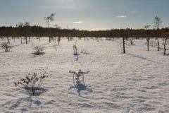 Quadcopter di DJI Phantow che sta sulla palude nevosa prima del decollo in Savonlinna, Finlandia Fotografia Stock