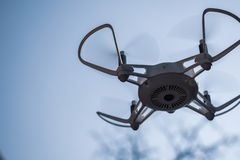 Quadcopter drone hovering in a blue sky royalty free stock images
