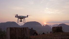 Quadcopter Drone Taking Off in Park at Beautiful Sunrise with Mountains on Background. Phang Nga, Thailand.