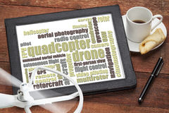 Quadcopter drone word cloud. On a digital tablet with a cup of coffee and rotating drone propeller stock images