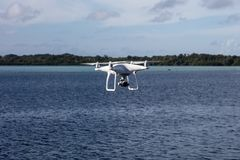 Quadcopter Flying Above the Sea. A quadcopter, or UAV or drone, flies above the ocean. Drones such as these allow the ability to view Earth`s landscapes and royalty free stock images