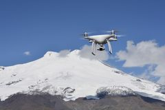 Quadcopter flying over mount Elbrus. royalty free stock photography